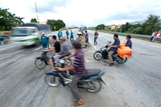 Người đi bộ và xe máy băng qua đường không đúng nơi quy định tiềm ẩn nguy cơ tai nạn giao thông - Ảnh: NAM TRẦN