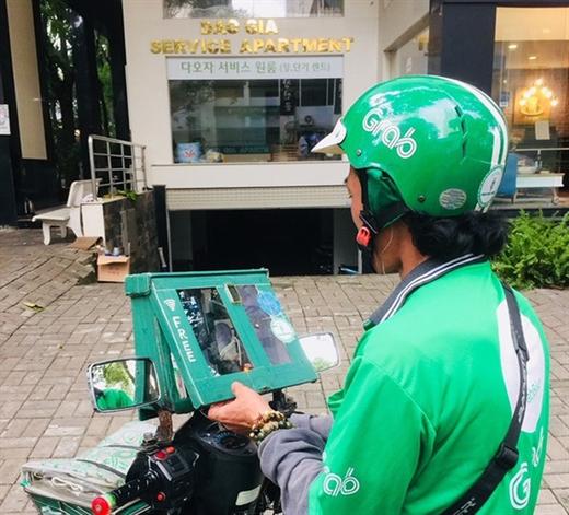 Anh tài xế xe ôm công nghệ với bộ phát sóng wifi miễn phí cho khách - Ảnh: LÊ THẢO