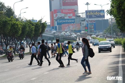 Vào giờ tan tầm, nhiều người thường đi thành nhóm, cắt ngang dải phân cách trên đường Điện Biên Phủ, Q.Bình Thạnh, TP.HCM - Ảnh: NGỌC PHƯỢNG