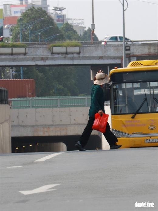 Tại khu vực bến xe An Sương, huyện Hóc Môn, TP.HCM người dân thường di chuyển cắt ngang đầu xe để ra vào bến xe - Ảnh: NGỌC PHƯỢNG