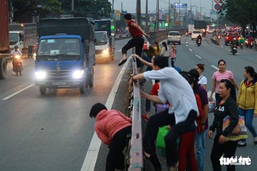 Cùng một đoạn dải phân cách nhưng người thì chui, người thì leo để băng qua đường trong làn xe lớn đang lao tới ngay trên quốc lộ 1A, Q.12, TP.HCM - Ảnh: NGỌC PHƯỢNG