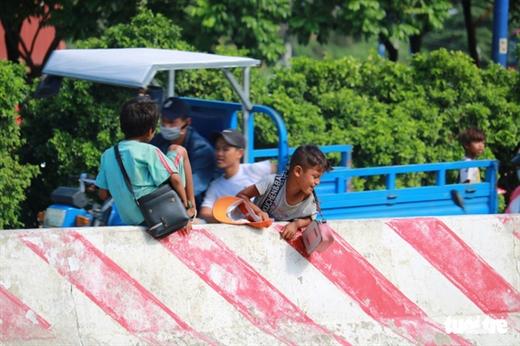 Những đứa trẻ hồn nhiên trèo qua dải phân cách ngay trên xa lộ Hà Nội, Q.2, TP.HCM - Ảnh: NGỌC PHƯỢNG