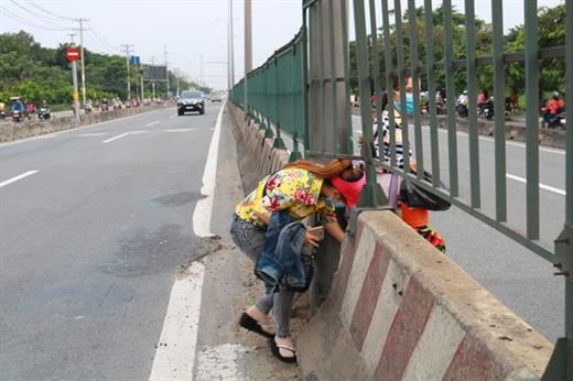 Trước một công ty tại Q.Bình Tân, TP.HCM, người đi bộ cũng chui cắt ngang dải phân cách trên QL1A để qua đường - Ảnh: NGỌC PHƯỢNG