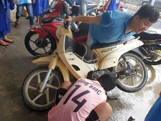 Bạn Nguyễn Huy (áo xanh) quyết định nghỉ chạy xe 1 ngày để hỗ trợ anh em sửa xe - Ảnh: DUY KHÁNH