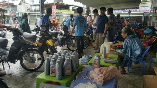 11h30 trưa 7-8 vẫn còn nhiều xe máy được người dân đem tới để thay nhớt và sửa chữa - Ảnh: DƯƠNG NGÂN
