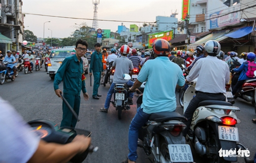 Cơ quan chức năng đứng làm dải phân cách để ngăn người dân lấn lên khi kẹt xe - Ảnh: LÊ PHAN