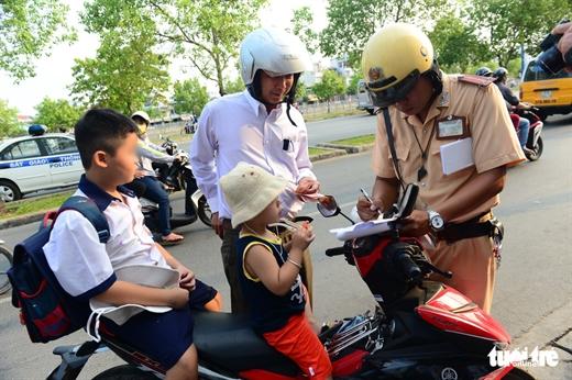 Cảnh sát giao thông xử phạt một trường hợp chở trẻ không đội mũ bảo hiểm trên đường Võ Văn Kiệt, Q.5, TP.HCM - Ảnh: QUANG ĐỊNH