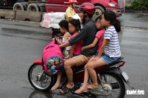 Vô tư chở 4 trẻ em không mũ bảo hiểm lại còn chạy ngược chiều trên quốc lộ - Ảnh: QUANG ĐỊNH