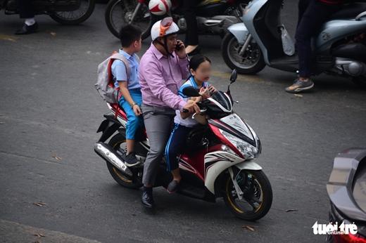 Một phụ huynh vừa nghe điện thoại vừa chở trẻ không đội nón bảo hiểm trên đường Nguyễn Thị Minh Khai, Q.3, TP.HCM - Ảnh: QUANG ĐỊNH