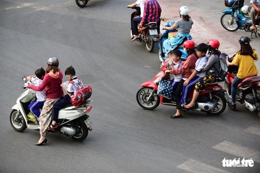 Chở trẻ không đội mũ bảo hiểm mà còn dừng xe không đúng vạch quy định khi chờ đèn đỏ trên đường Nguyễn Bỉnh Khiêm, Q.1, TP.HCM - Ảnh: QUANG ĐỊNH