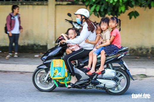 Người phụ nữ chở 4 đứa trẻ nhưng không em nào được mang mũ bảo hiểm - Ảnh: THANH YẾN