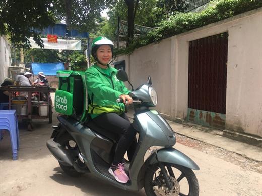 Chị Nguyễn Thị Ngọc Dung đang trên đường đi giao thức ăn cho khách hàng - Ảnh: MINH PHƯỢNG