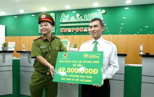 Công an phường Bến Nghé trao lại 49 triệu đồng cho tài xế Hoàng Gia Thái - Ảnh: N.H.
