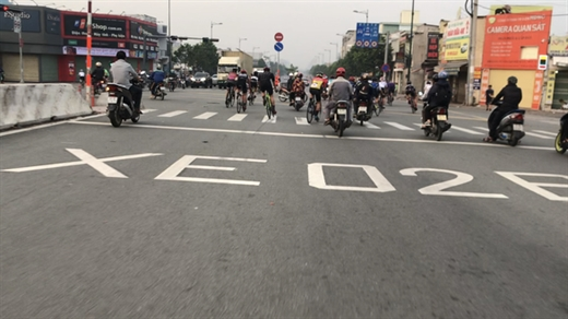 Nhóm người đi xe đạp tốc độ cao lạng lách, vượt qua một giao lộ trên đường Phạm Văn Đồng - Ảnh: LÊ PHAN