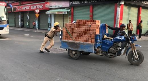 Thiếu tá Nguyễn Thanh Sơn đẩy xe cho người dân - Ảnh: LÊ PHAN
