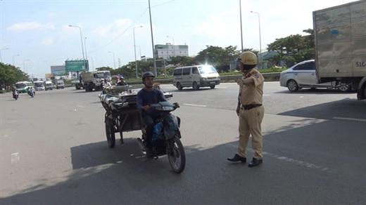 Cảnh sát giao thông xử lý tình trạng sử dụng xe ba, bốn bánh chở hàng cồng kềnh - Ảnh: MINH HÒA