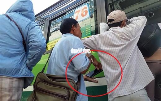Hai người đàn ông dàn cảnh móc trộm điện thoại của bà cụ tại trạm chờ xe buýt gần khu vực cầu bộ hành khu du lịch Suối Tiên (phường Linh Trung, quận Thủ Đức) vào sáng 14-10 - Ảnh: MINH HÒA