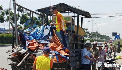 Lực lượng chức năng tháo dỡ dãy quán tạm bợ tại khu vực trạm chờ xe buýt gần cầu bộ hành KDL Suối Tiên trưa 17-10 - Ảnh: MINH HÒA
