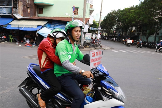 Anh Quí cố gắng giảm ga, chạy rất chậm để đảm bảo an toàn cho bà cụ ngồi phía sau - Ảnh: NGỌC PHƯỢNG