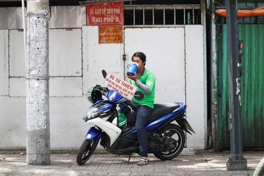 Sau những chuyến xe, anh Quí nghỉ tạm bên vệ đường ở quận Phú Nhuận chờ khách - Ảnh: NGỌC PHƯỢNG